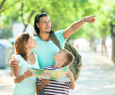 Man showing the way on the map for family at park  photo