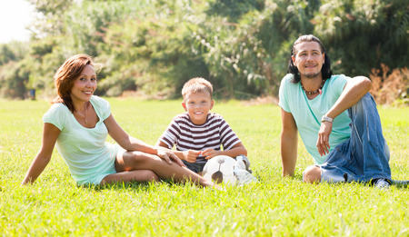 Happy couple with teenager child  enjoying time at city park photo