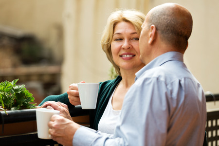 Mature couple having morning coffee at balcony and smiling photo