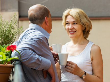Happy mature couple drinking coffee and discussing at balcony photo