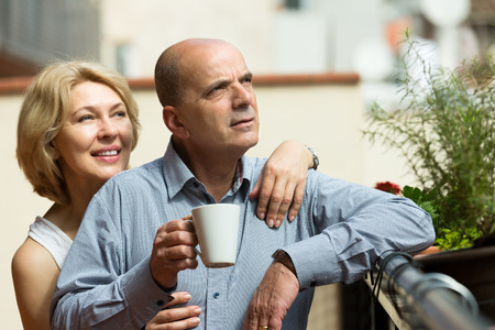 Aged couple staying on balcony with tea cups in hands  photo