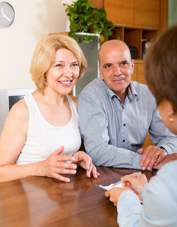 Smiling mature couple of pensioners talking with employee at office photo