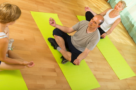 freetime: Positive elderly couple practicing yoga with female instructor
