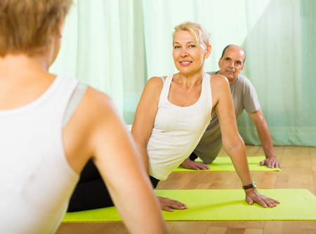 Trainer showing happy elderly couple how to incline the body Stock Photo - 30540352