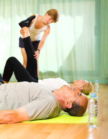 mature people: Young female instructor helping mature people to stretch Stock Photo