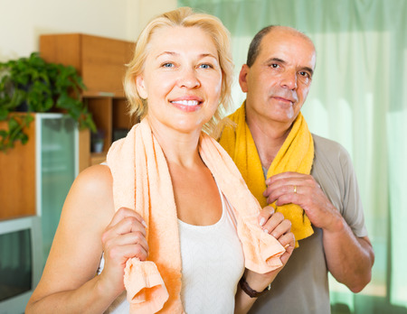 spouses: Positive senior spouses smiling after training indoor. Focus on woman