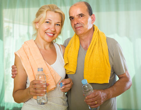 spouses: Positive mature spouses drinking water after fitness at home and smiling  Stock Photo
