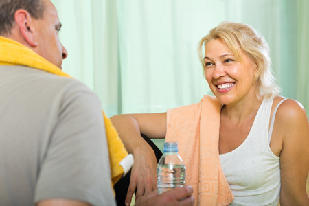 spouses: Happy smiling senior spouses drinking water after fitness at home