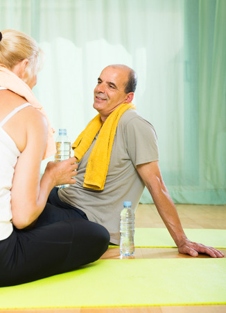 Mature spouses with bottles of water smiling after morning exercises  photo
