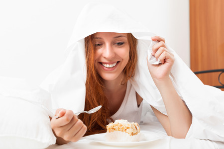 furtively: Happy young woman eating sweet cake under sheet in bed