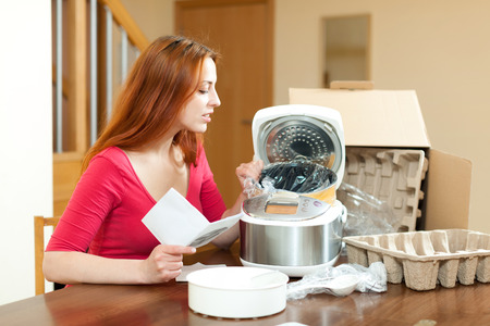 Young woman unpacking and reading user manual for new crock-pot at home photo