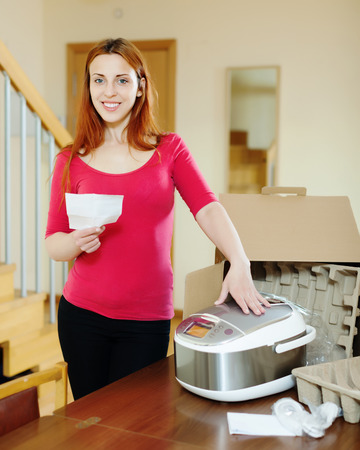 cheerful woman  reading manual for new slow cooker at home interior photo