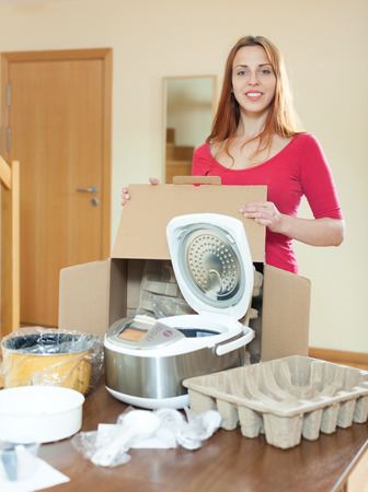 Young  housewife unpacking new multicooker in home photo