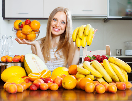 Positive   long-haired woman with bananas and other fruits in home photo