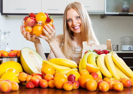 woman with heap of various fruits in  kitchen  photo