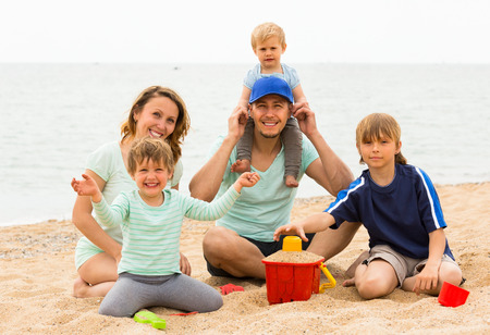 Happy family of five playing with sand on the beach at sea shore photo