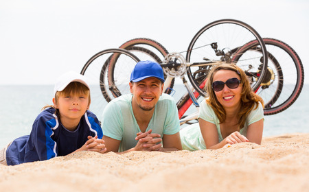 ciclos: Pareja con hijo adolescente acostado en la orilla del mar en d�a de verano con ciclos detr�s