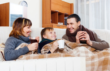 Happy parents and teenage son warming near warm heater in home Stock Photo