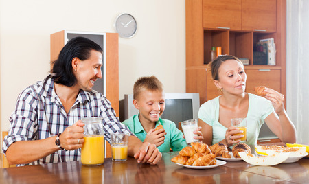 Happy couple with teenager child during breakfast in home interior photo