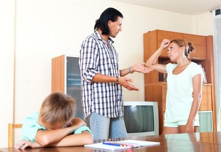 Man with wife and teenage boy having quarrel photo