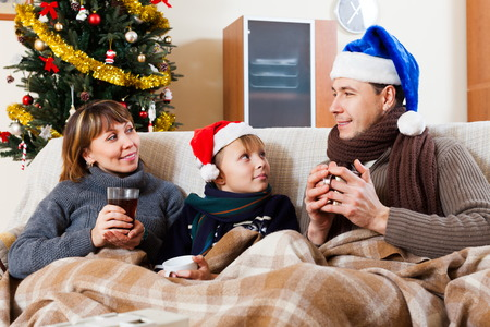 Happy family with cups of tea and Christmas tree at home