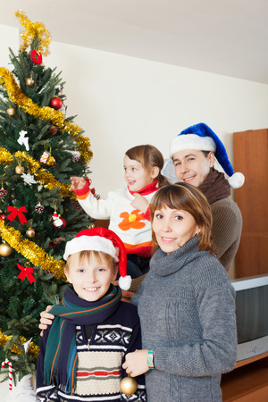 Happy family of four with  Christmas tree at home photo