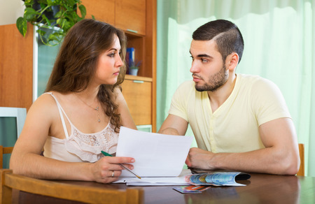 utility payments: Young couple  with money and financial documents in home interior