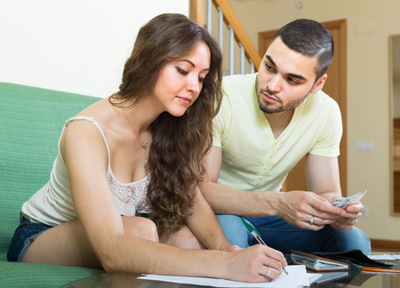 Young married couple sitting on sofa and calculating the family budget   photo