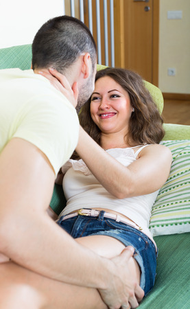 Loving couple kissing and playing on sofa at home photo