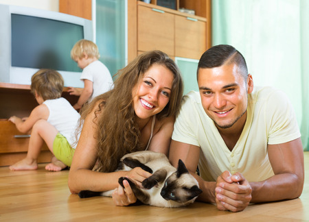 Happy family of four playing with kitten on the floor indoor photo