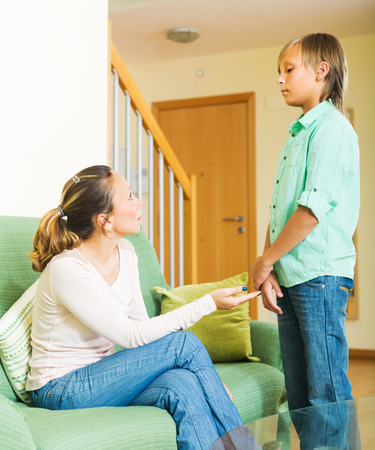 Ordinary mother berating teenager son in living room at home. Focus on mother  Stock Photo