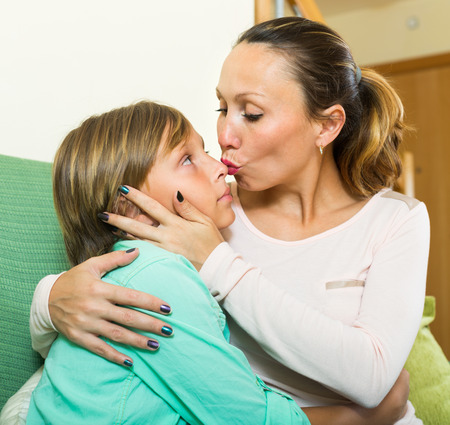 young parents: middle-aged woman consoling crying teenage son at home