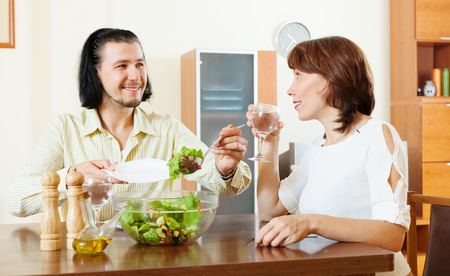 happy middle-aged couple eating vegetarian salad with water at home photo