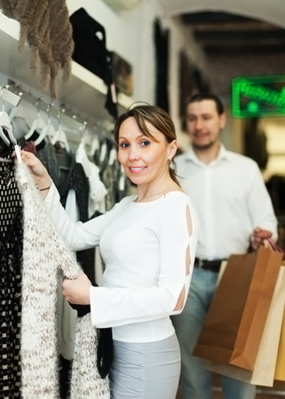 couple choosing clothes at fashion market together photo