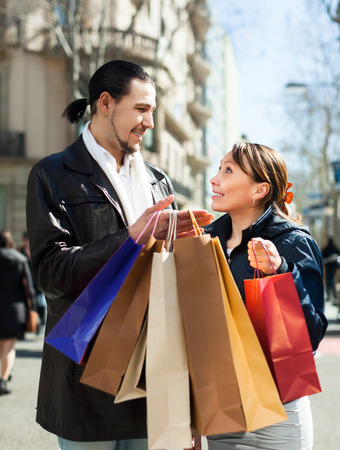 cheerful man and woman with shopping bags at street photo