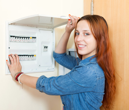 turns of the year: Long-haired woman turning off the light-switch at power control panel in home