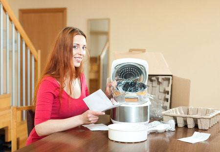 Woman with electric crock pot in her kitchen at home photo