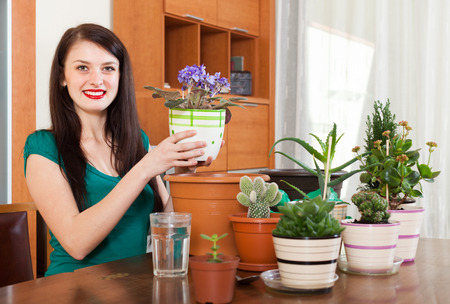 Smiling girl working with  viola flowers in pots  photo