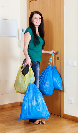 Happy brunette woman near door with garbage bags at home photo