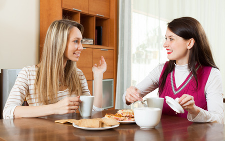 blabber: young women table gossiping and drinking tea in home Stock Photo