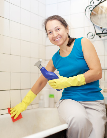 Smiling  mature woman cleans bathtub with sponge in bathroom at home  photo