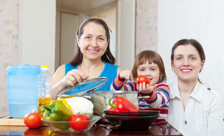 Happy family together cooking veggie lunch with vegetables at home photo