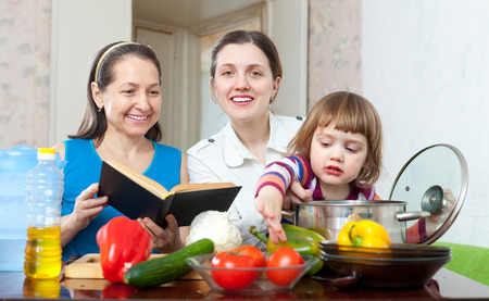 three generations of women:  three generations of happy women cook vegetables in the kitchen