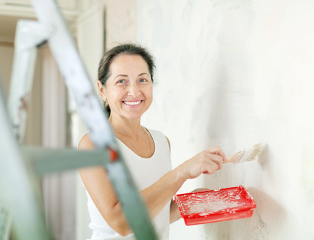 Happy mature woman makes repairs at home photo