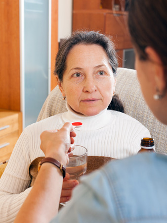Woman giving the cough syrup to elderly mother photo