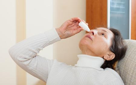 nasal drops: Mature woman dripping nasal drops  Stock Photo
