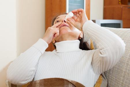 nose drops: Senior woman dripping nasal drops at home Stock Photo
