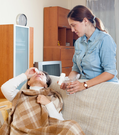 nose drops: Mature woman dripping nasal drops. Adult daughter takes care
