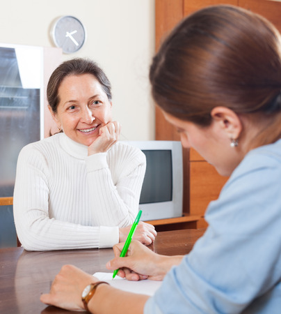 Smiling mature woman questionnaire for social worker or employee at table Banque d'images