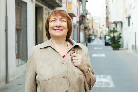 portrait of smiling mature woman at european town street Stock Photo - 30930563